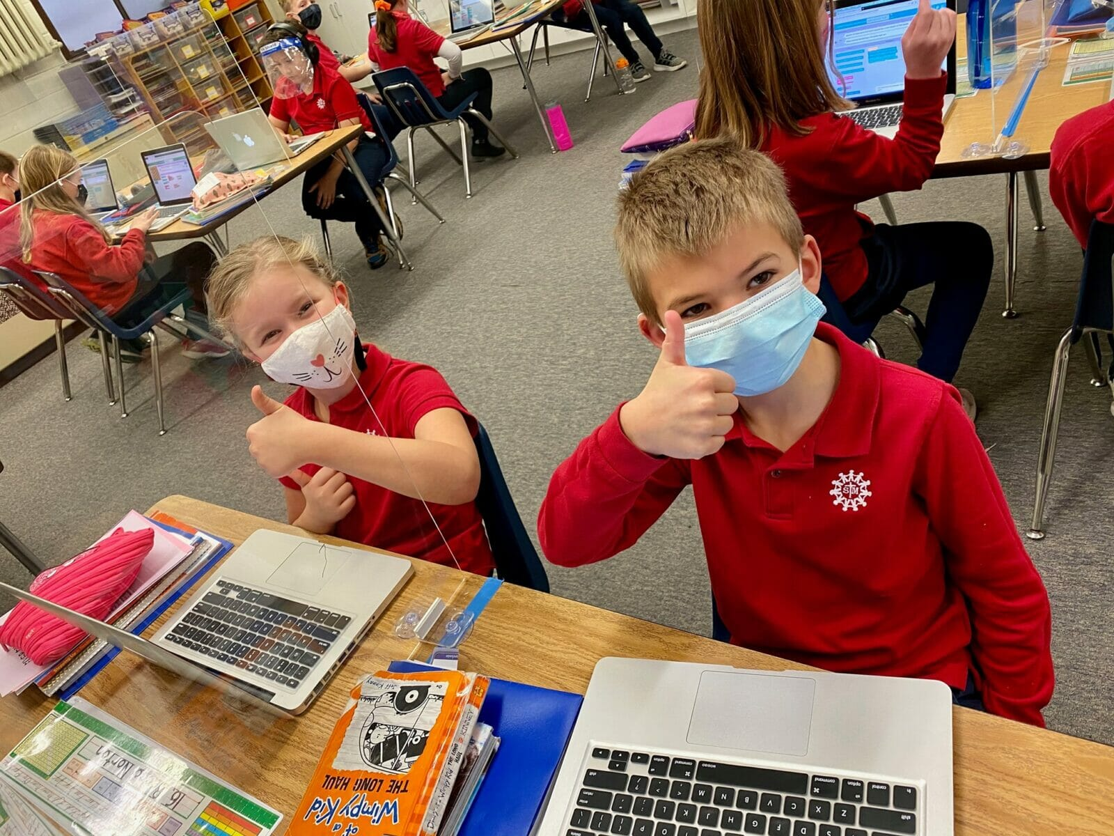 Catholic school students in masks giving thumbs up